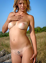 Sexy girl with amazing big boobs and a tattoo on the pubis shows off her assets outdoors.